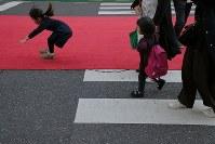レッドカーペットが敷かれた道路で飛び跳ねる子ども=東京都渋谷区で2018年10月21日午後3時16分、和田大典撮影