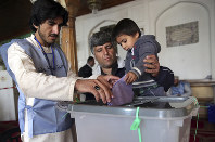 A man lets his child cast his vote in Parliamentary elections in the old city of Kabul, Afghanistan, Saturday, Oct. 20, 2018. Tens of thousands of Afghan forces fanned out across the country as voting began Saturday in the elections that followed a campaign marred by relentless violence. (AP Photo/Massoud Hossaini)