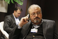 In this Jan. 29, 2011 file photo, Saudi journalist Jamal Khashoggi speaks on his cellphone at the World Economic Forum in Davos, Switzerland. Eighteen days after Khashoggi disappeared, Saudi Arabia acknowledged early Saturday, Oct. 20, 2018, that the 59-year-old writer has died in what it said was a