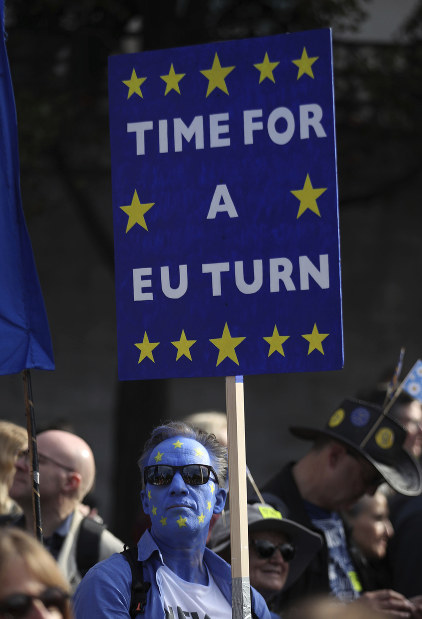 An anti-Brexit campaigner with his face painted in the colors of the European Union flag is seen during the People's Vote March, in London, Saturday Oct. 20, 2018. (Yui Mok/PA via AP)