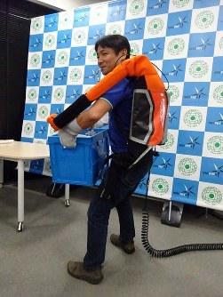 作業支援ロボット「マッスルアッパー」で重さ20キロの荷物を軽々と持ち上げる男性=東京都新宿区の東京理科大で2018年10月16日、斎藤有香撮影