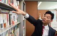 議員会館事務所で書棚の本を説明する西村康稔官房副長官=丸山博撮影