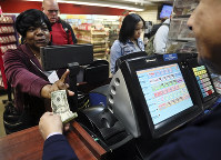 Annette Gray, left, from Valley Stream, N.Y., buys lottery tickets on Oct. 19, 2018, in New York. (AP Photo/Bebeto Matthews)