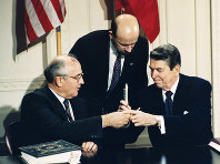 In this Dec. 8, 1987 file photo U.S. President Ronald Reagan, right, and Soviet leader Mikhail Gorbachev exchange pens during the Intermediate Range Nuclear Forces Treaty signing ceremony in the White House East Room in Washington, D.C. Gorbachev's translator Pavel Palazhchenko stands in the middle. (AP Photo/Bob Daugherty, File)