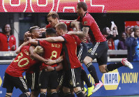 Atlanta United players mob Franco Escobar after his goal for a 1-0 lead over the Chicago Fire during the first half in a MLS soccer match on Oct 21, 2018, in Atlanta. (Curtis Compton/Atlanta Journal-Constitution via AP)