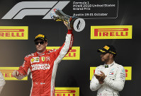 Ferrari driver Kimi Raikkonen, of Finland, holds the trophy after winning the Formula One U.S. Grand Prix auto race at the Circuit of the Americas, on Oct. 21, 2018, in Austin, Texas. (AP Photo/Eric Gay)