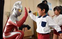 ウルトラセブンとハイタッチを交わす園児たち=岡山県倉敷市真備町で2018年10月22日、益川量平撮影