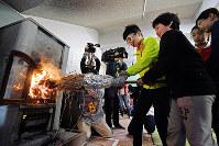 自分たちでおこした火を使ってストーブに点火する児童たち=神戸市灘区の市立六甲山小学校で2018年10月23日午前10時1分、小松雄介撮影