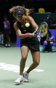 Naomi Osaka of Japan makes a backhand return to Sloane Stephens of the United States during their women's singles match at the WTA tennis tournament in Singapore, on Oct. 22, 2018. (AP Photo/Vincent Thian)
