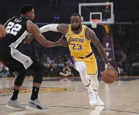 Los Angeles Lakers forward LeBron James, right, drives toward the basket as San Antonio Spurs forward Rudy Gay defends during the first half of an NBA basketball game on Oct. 22, 2018, in Los Angeles. (AP Photo/Mark J. Terrill)