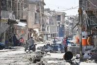 激戦地となり、多くの建物が破壊されたモスル旧市街。かろうじて原形をとどめた建物の1階で小さな飲食店が営まれ、子どもを抱いた男性らが談笑していた。街は至る所にがれきが散乱し、車やバイクが通るたびに粉じんが舞った=イラク・モスル旧市街で2018年8月10日、木葉健二撮影