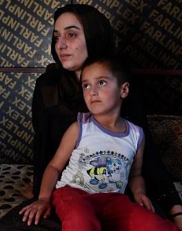 クルド自治政府の治安部隊「ペシュメルガ」所属だった夫サバハさんをISとの戦闘で亡くしたヤジディー教徒のハウラさん(奥)と息子のサムハ君。キャンプで悲しげな表情を浮かべる=イラク・ドホーク県ハンケで2018年8月22日、木葉健二撮影