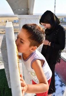 クルド自治政府の治安部隊「ペシュメルガ」所属だった父サバハさんの墓石に口づけする、ヤジディー教徒のサムハちゃん(4)。父は2015年11月、ISとの戦闘で死んだ。毎週サムハちゃんと墓を訪れる母ハウラさん(25)=右奥=は墓前で目を潤ませた。「サムハも私もまだ幼いの。あなたのいない人生はとてもつらいです」=イラク・ドホーク県ハンケで2018年8月22日、木葉健二撮影
