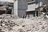 激戦地となり、多くの建物が破壊されたモスル旧市街で袋を担いで歩く少年たち。がれきには今も爆発物が残る可能性がある=イラク・モスル旧市街で2018年8月10日、木葉健二撮影