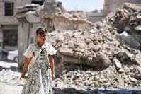 建物が破壊されたモスル旧市街を歩く女の子。イラク軍によって解放された今もISの戦闘員が潜み、住民は危険と隣り合わせで過ごす=イラク・モスル旧市街で2018年8月10日、木葉健二撮影