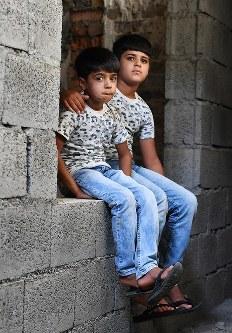 アランドさん(9歳、右)とアルウィンちゃん(6)兄弟は2015年、ペシュメルガ所属だった父がISとの戦闘の末に拘束され、殺害された。「父さんに会いたい」。アランドさんはうつむいた。父の遺体はまだ戻ってきていない=イラク・スレイマニヤ県チャムチャマルで2018年8月27日、木葉健二撮影