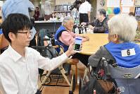 ベストを着用した高齢者から、心拍数などのデータを収集する推進協議会の関係者=高松市鶴市町で、山口桂子撮影
