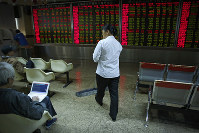 A cleaner walks by as investors monitor stock prices at a brokerage house in Beijing, on Oct. 24, 2018. (AP Photo/Andy Wong)