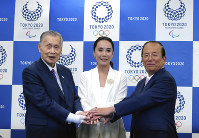 Japanese film director Naomi Kawase, center, Tokyo Olympic organizing committee President Yoshiro Mori, left, and Toshiro Muto, right, CEO of the Tokyo Organizing Committee of the Olympic and Paralympic Games, pose for photographers during a press conference in Tokyo, on Oct. 23, 2018. (AP Photo/Eugene Hoshiko)