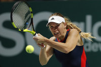 Caroline Wozniacki of Denmark plays a return shot while competing against Petra Kvitova of the Czech Republic during their women's singles match at the WTA tennis finals in Singapore, on Oct. 23, 2018. (AP Photo/Vincent Thian)