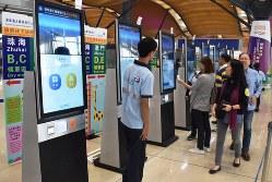 珠海やマカオ行きのチケットを買う人たち=香港国際空港沖の人工島で2018年10月24日、福岡静哉撮影
