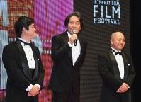 第31回東京国際映画祭のステージに登壇し、あいさつする俳優の役所広司さん。左は沖田修一監督、右は白石和彌監督=東京都港区で2018年10月25日午後5時12分、藤井太郎撮影