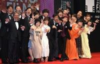 第31回東京国際映画祭のステージに登壇し、ポーズをとる映画「カメラを止めるな!」の上田慎一郎監督(前列右から3人目)ら制作スタッフ、出演者ら=東京都港区で2018年10月25日午後4時35分、藤井太郎撮影