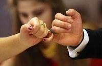 結婚披露宴で花婿と小指を絡めて手をつなぐメリエム・ドガンさん(左)=埼玉県川口市で2018年9月30日、宮武祐希撮影