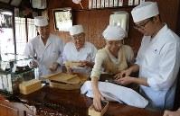 店頭では家族が並んで作っている。(左から)森藤さん、与八郎さん、春美さん、淳平さん=京都市上京区で