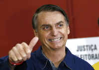 In this Oct. 7, 2018 file photo, presidential frontrunner Jair Bolsonaro, of the Social Liberal Party, flashes a thumbs up at a polling station in Rio de Janeiro, Brazil. (AP Photo/Silvia Izquierdo)