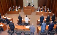 議員定数削減の改正条例案の採決で、立ち上がって賛成を表明する輪島市議ら=石川県輪島市議会で、石川将来撮影
