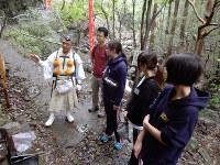 課外授業として僧侶から旧跡の説明を聞く野呂靖さん(左から2人目)ら=大阪府泉佐野市で、玉木達也撮影