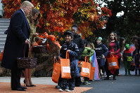 U.S. President Donald Trump and first lady Melania Trump give candy to children during a Halloween trick-or-treat event at the White House, on Oct. 28, 2018, in Washington. (AP Photo/Jacquelyn Martin)