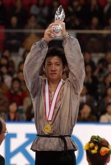 【2001年】男子シングルを制しトロフィーを掲げる本田武史=くまもとアクアドームで2001年12月2日、西村剛撮影