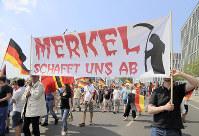 「メルケルが我々を滅ぼす」と書かれた横断幕を掲げ、難民受け入れ政策を批判するAfD支持者=ベルリンで2018年5月27日、中西啓介撮影