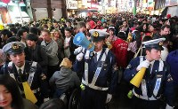 Police officers and other authorities ask people to act in a safe manner at Shibuya Center Street, a famous shopping arcade, in Tokyo's Shibuya Ward on Oct. 31, 2018. (Mainichi/Daisuke Wada)