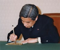 元号を平成に改める政令の書類に署名される天皇陛下=宮殿の鳳凰の間で1989年1月7日(代表撮影)