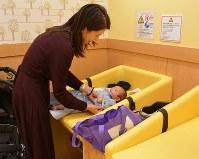 イオンスタイル板橋前野町の「赤ちゃんの駅」でおむつ替えを済ませる親子=東京都板橋区で