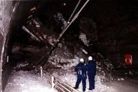 【豊浜トンネル事故】北海道古平町の国道の豊浜トンネルで岩盤が崩落し、小中高校生8人を含む19人が乗った路線バスなど2台が下敷きとなり、20人が死亡した。写真は巨岩がバスや乗用車をのみ込んだ現場を調べる対策本部係官=豊浜トンネル古平側で1996年2月10日撮影