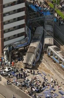 【JR福知山線脱線事故】JR福知山線で快速列車が制限時速70キロのカーブにジソク115キロで進入。一部が脱線し線路脇のマンションに激突した。乗客106人と運転士が死亡し、562人が負傷した。写真は進行方向左側のマンションに激突、大破した電車と運び出される大勢の負傷者=兵庫県尼崎市潮江4で2005年4月25日午前9時47分、本社ヘリから関口純撮影