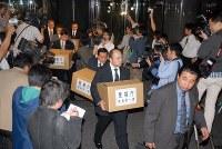 【東京・芝エレベーター死亡事故】東京都港区のマンションで、エレベーターの扉が開いたまま上昇し、降りようとした高校2年の男子生徒が床と外枠の間に挟まれ死亡した。エレベーターは「シンドラーエレベータ」製で、写真は同社の入っているビルから押収物を運び出す捜査員=東京都江東区越中島で2006年6月7日午後9時1分、尾籠章裕撮影