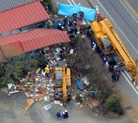 【鹿沼クレーン車暴走事故】栃木県鹿沼市の国道で集団登校中の児童の列にクレーン車が突っ込み、小学4~6年の児童6人がはねられ死亡した。写真は児童たちがクレーン車(中央)になぎ倒された現場。右は事故処理のクレーン車=栃木県鹿沼市で2011年4月18日午前9時55分、本社ヘリから小林努撮影