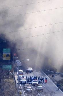 【笹子トンネル天井板崩落事故】中央自動車道上り線笹子トンネル内で、コンクリート製の天井板約340枚が約140メートルにわたって落下。車3台が下敷きになり、男女9人が死亡、3人が負傷した。写真は崩落事故があった中央自動車道上り線の笹子トンネルから立ち上る煙=山梨県甲州市で2012年12月2日午前9時49分、本社ヘリから