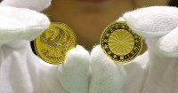 天皇陛下在位30年記念硬貨の1万円金貨。左が表側=大阪市北区の造幣局で2018年11月5日、梅田麻衣子撮影