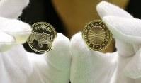 天皇陛下在位30年記念硬貨の500円銅貨。左が表側=大阪市北区の造幣局で2018年11月5日、梅田麻衣子撮影