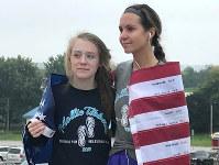 不法移民に殺害されたモリー・ティベッツさんのために米国旗を掲げて走ったいとこのモーガン・コラムさん(右)と後輩エマ・アレクサンダーさん=米中西部アイオワ州ブルックリンで2018年9月30日、國枝すみれ撮影