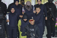 Vietnamese Doan Thi Huong, top, and Indonesian Siti Aisyah are escorted by police as they leave the Shah Alam High Court after a hearing in Shah Alam, Malaysia, on Nov. 7, 2018. (AP Photo/Yam G-Jun)