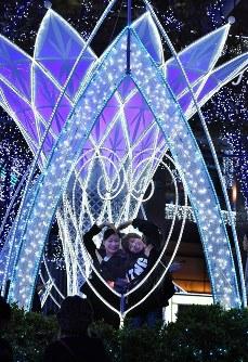 JR博多駅前のイルミネーションを背景に写真撮影する人たち=福岡市博多区で2018年11月8日午後8時11分、徳野仁子撮影