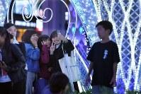 JR博多駅前のイルミネーションを背景に写真撮影する人たち=福岡市博多区で2018年11月8日午後7時12分、徳野仁子撮影