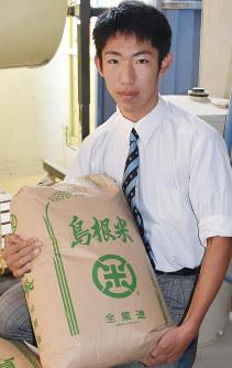 栽培した米を持つ中村諒一さん=島根県出雲市の出雲農林高校で、山田英之撮影
